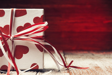 Close up of gift box over red wooden background