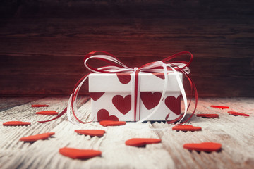 Gift box with red hearts over wooden background