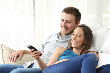 Happy couple watching tv at home