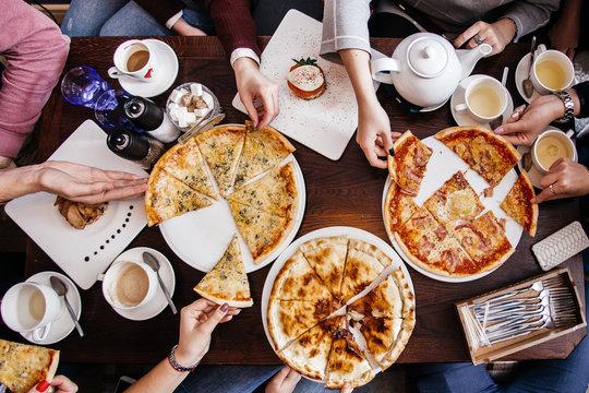 Компания людей за столом едят пиццу.