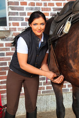 Young Woman Saddling Her Horse