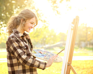 Young female artist painting picture in autumn park