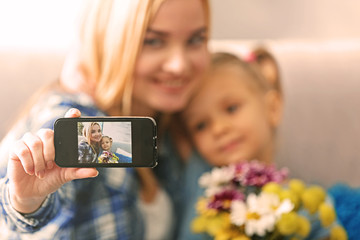 Young woman with daughter taking selfie at home, close up. Mother's day concept