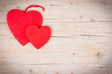 Two red hearts on wooden background