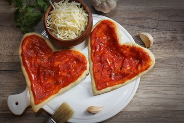 Heart shaped pizza ready to bake overhead view