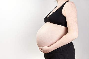 Pregnant woman belly over white background