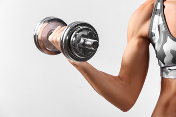 Sporty young woman with dumbbell on gray background