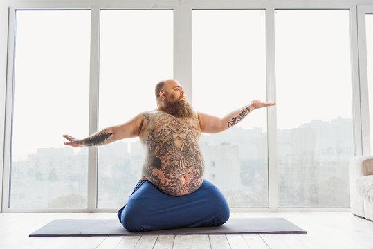 Man meditating near window