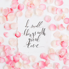 Do small things with great love. Inspirational quote made with calligraphy and floral pattern with pink rose petals. Flat lay, top view