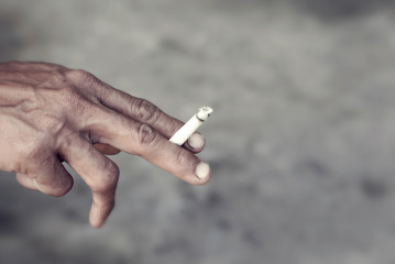 Asian man hand holding a burning cigarette between his two finger