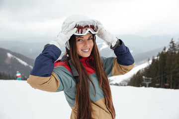 Pretty young lady snowboarder on the slopes frosty winter day