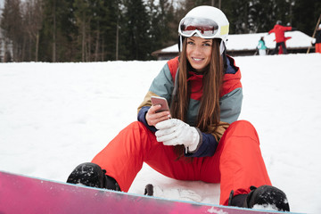Happy lady snowboarder lies on the slopes chatting by phone.