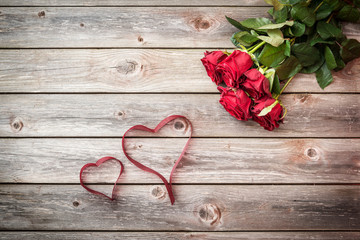 bouquet of red roses on wood background with hearts from ribbon.
