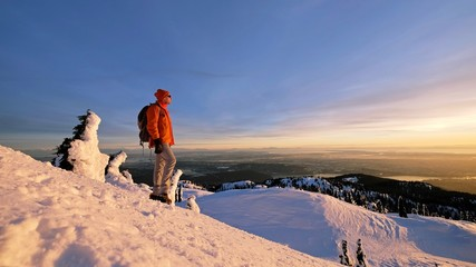 Man snowshoeing on mountain top watching sunset. Mount Seymour Provincial Park. Vancouver. British Columbia. Canada.