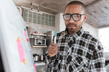 African businessman wearing glasses in office working with flipchart