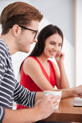Vertical image of happy couple by the table with laptop