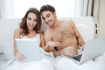 Couple with laptop and tablet talking in bed