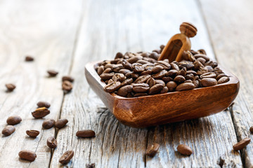 Roasted coffee beans in a wooden bowl.