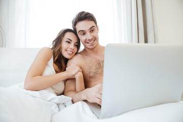 Couple hugging and using laptop in bed