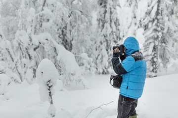 Photographer in blue jacket in winter woods