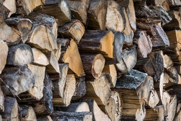 Chopped firewood, stacked woodfuel, fuelwood texture. Natural wooden background.