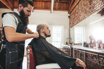 Barber covering client with salon cape