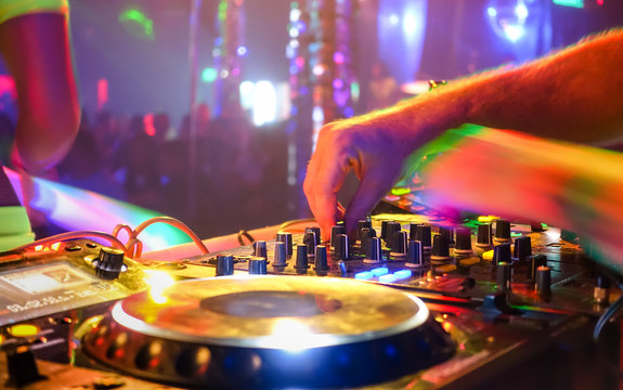 Close up of dj playing party music on modern cd usb player in disco club - Nightlife and entertainment concept - Defocused background with shallow depth of field and focus on buttons near mixing hand