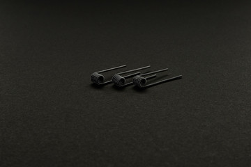 Clapton coil for vaping on a black background macro closeup wire steel