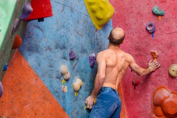 Free climber bald amateur man climbing artificial boulder indoors, back view