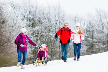 Familie mit Kindern im Schnee bei Winter Spaziergang