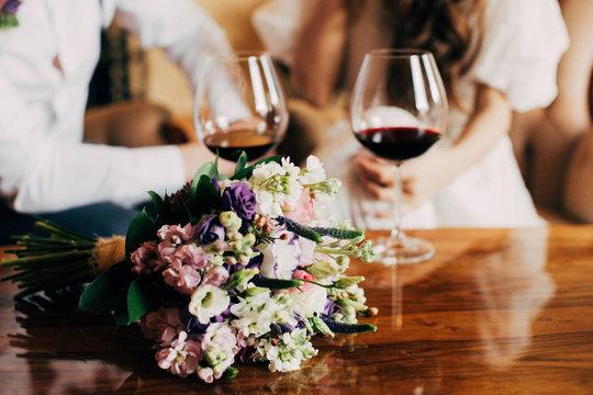 Wedding bouquet near to glass of red wine