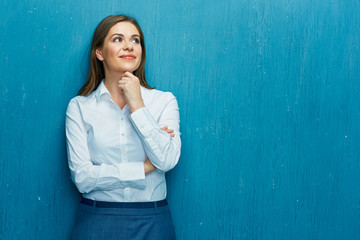 Smiling young business woman portrait on blue wall background.