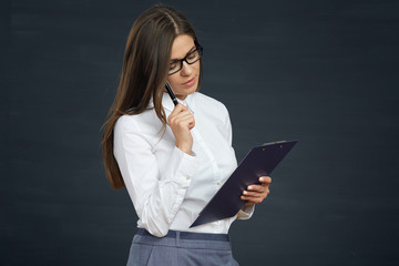 beautiful young woman holding clipboard with pen thinking.