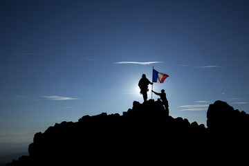Two soldiers raise the French flag on top of the mountain