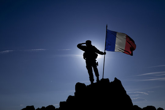 Soldier on top of the mountain with the French flag