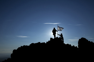 Two soldiers raise the Israeli flag on top of the mountain