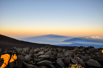 Stunning sunrise seen from summit of Haleakala at 3055 meters above sea level. In the background you can see the massive shadow of Haleakala projected on West Maui and the Pacific Ocean. Maui, Hawaii.