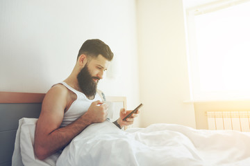 Bearded man lying in bed with morning coffee and phone using app