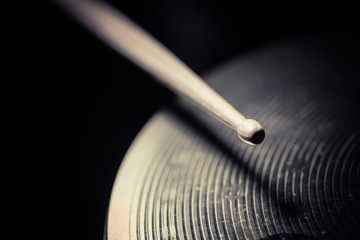 Close up shot of a drumstick hitting a cymbal.