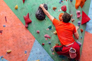 young caucasian amateur man rock climbing indoors at gym