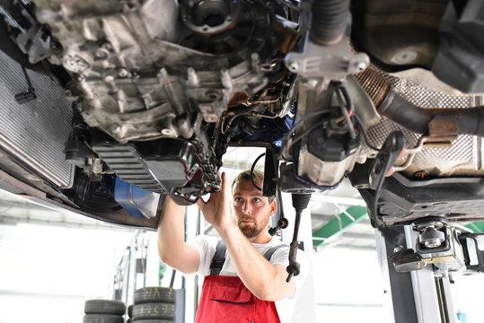 Automechaniker repariert defektes Fahrzeug auf der Hebebühne in einer Werkstatt