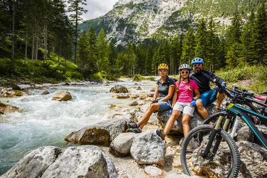 Family bike rides in the mountains while relaxing on the riverba