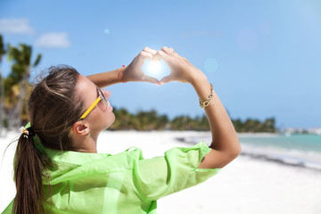 Woman standing on white sand making a hart shape with fingers.