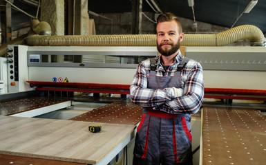 Carpenter works on wood plank in carpentry workshop