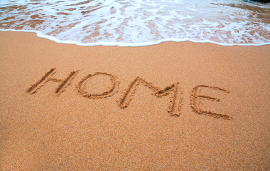 "written words "" home "" on sand of beach with wave on background"