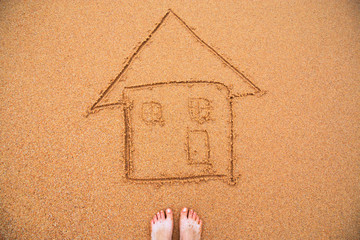 painted home on sand of beach with feets