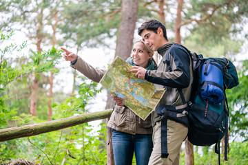Junges Paar, Frau und Mann, beim Wandern suchen den richtigen Weg mit Wanderkarte