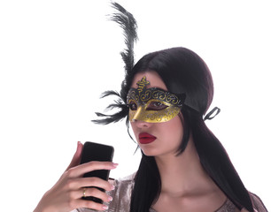 studio portrait of a girl in a carnival mask and with telephone isolated on white background