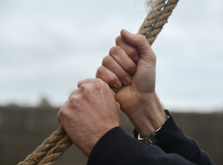 man's hands holding rope