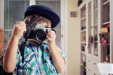 Cute little boy in retro outfit taking pictures with old film camera. Supporting creativity, learning by doing, creative leisure for children.